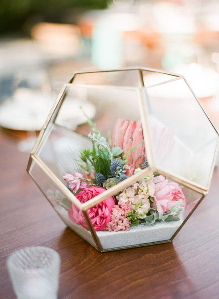 a summer inspired plant terrarium with pink and green florals inside