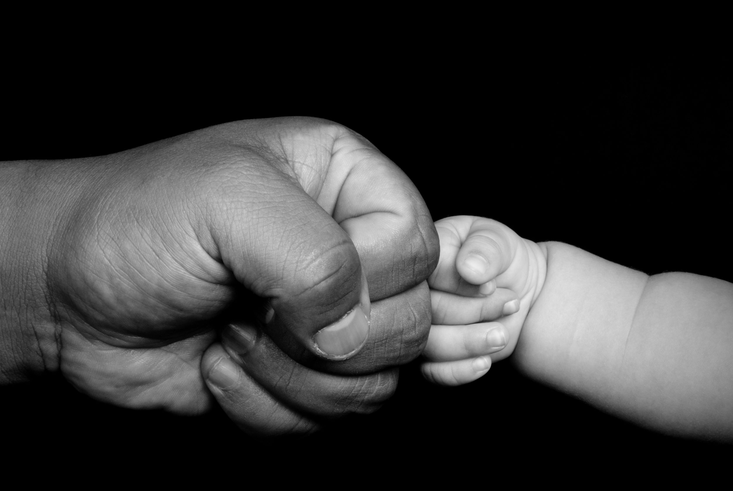 baby fist bumping his dad