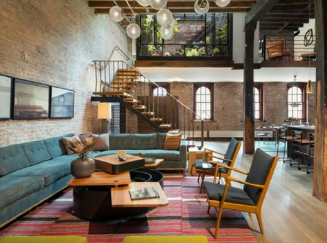 exposed brick loft interior with a colourful rug and armchairs