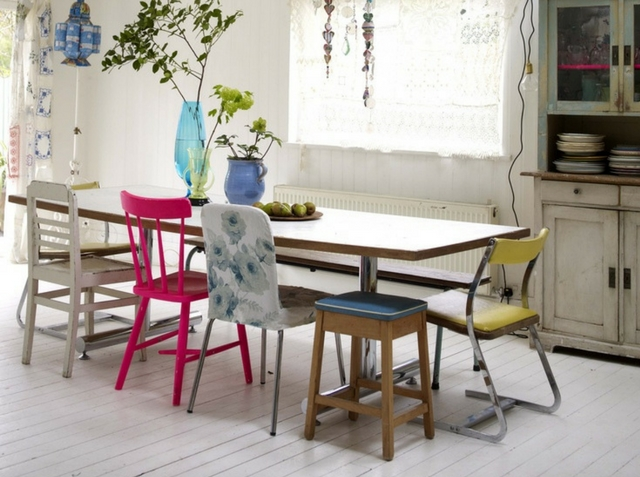 a vintage loft interior with mismatched chairs at a dining table