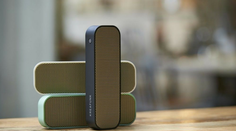 music speakers on top of wooden table with blurred background