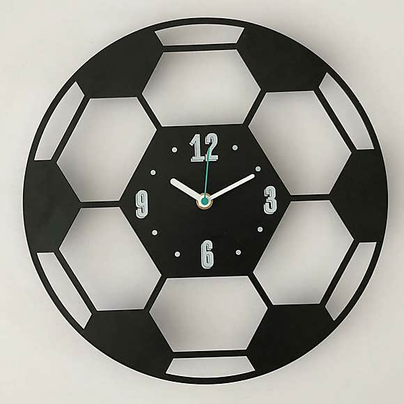 wall clock shaped like a football with cut out details