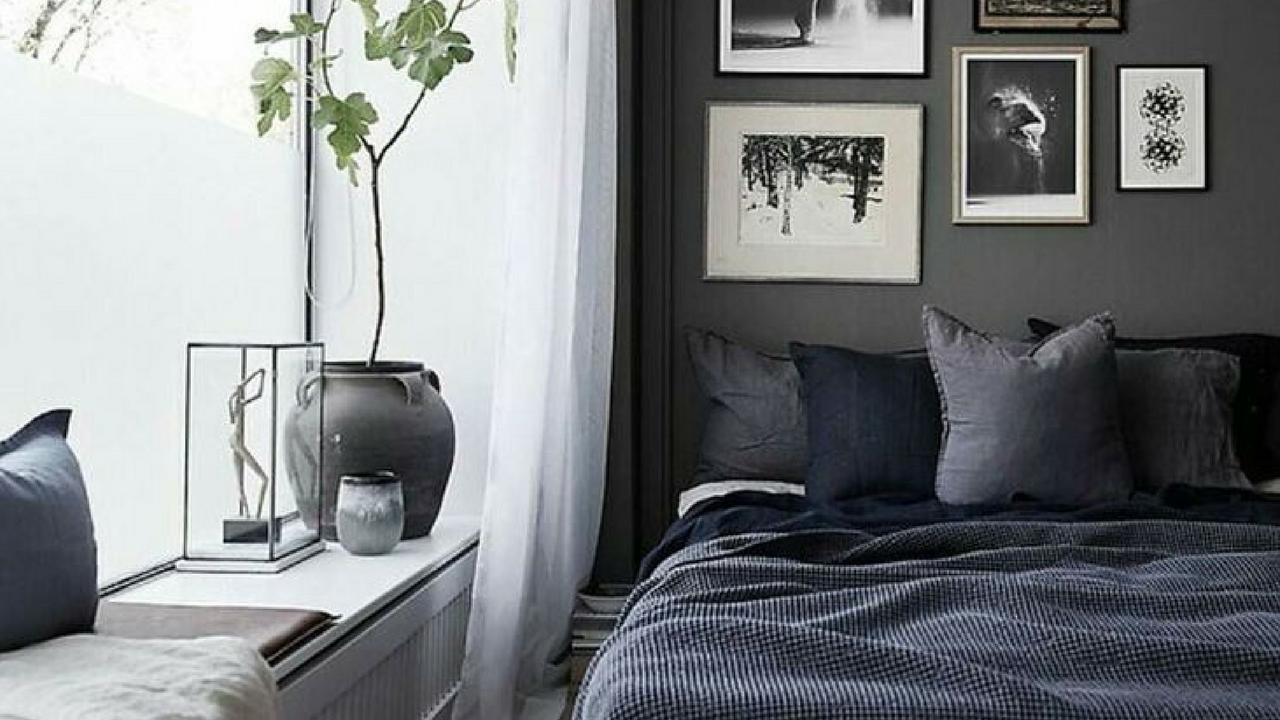 dark colours muted grey coloured walls with black and white artwork in a large bedroom