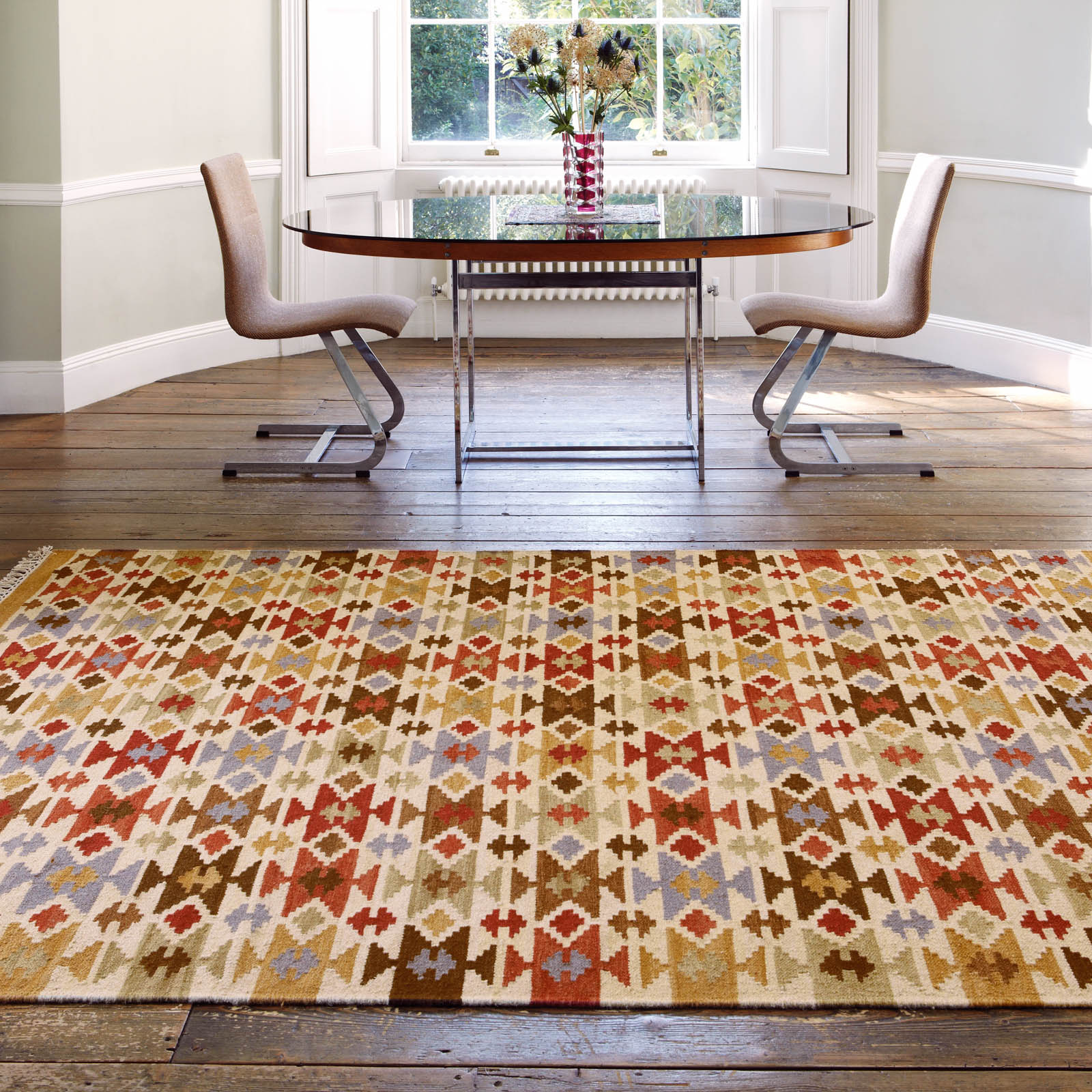 patterened kilim rug on wooden dining room floor next to glass plated table and chairs