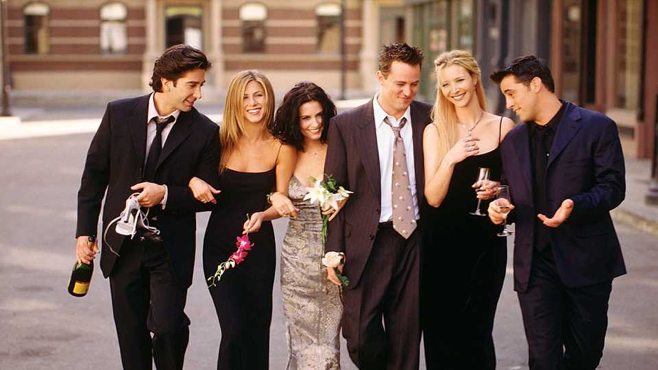 friends cast in suits and dresses