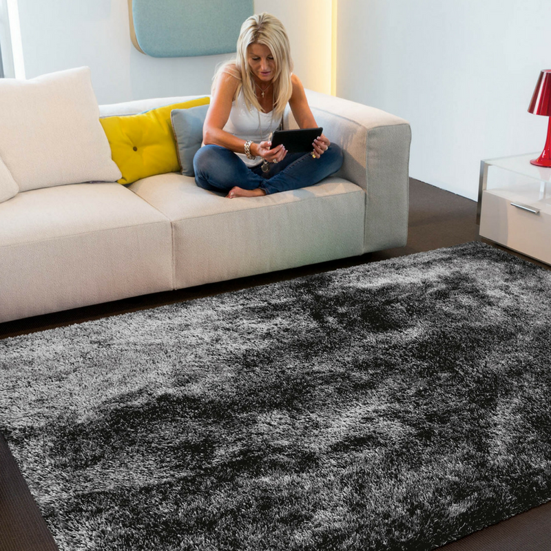 grey shaggy rug with a woman sitting on a couch reading a book