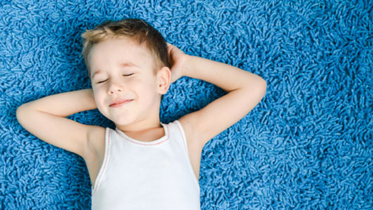 little boy with rug allergies laying on a blue shaggy rug