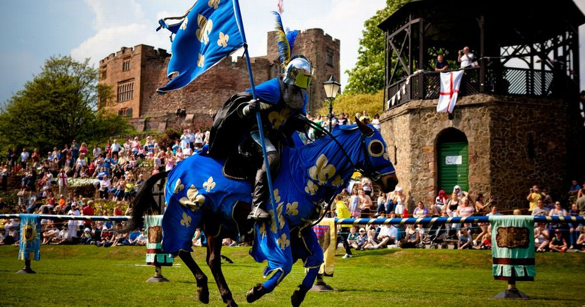 St. George's Day jousting event with a man in blue riding a dark brown horse