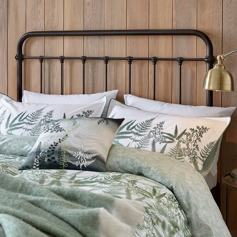 the costa rica fern bedding set on a bed with a black bed frame against a wooden wall