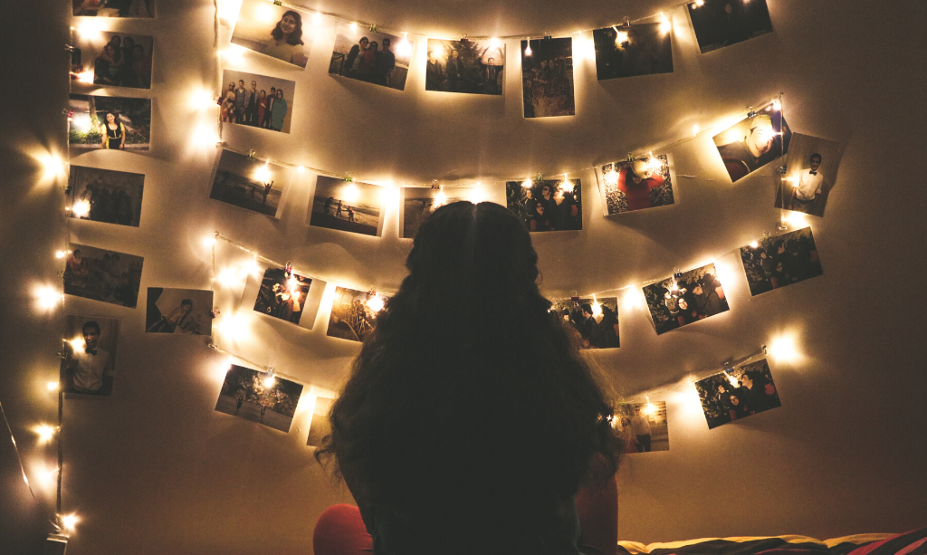 Fairy lights on a wall with hanging photos