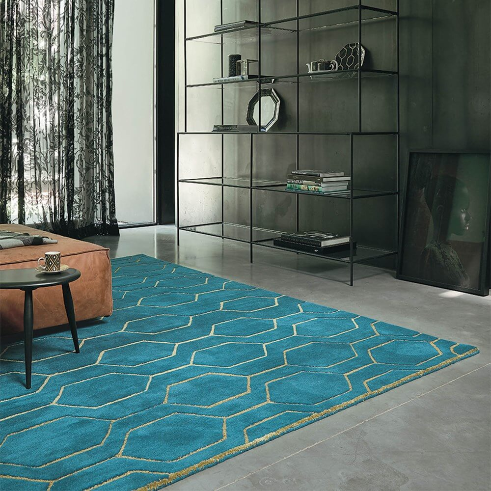 A blue teal arris rug in a living room with table and chairs set on top of it
