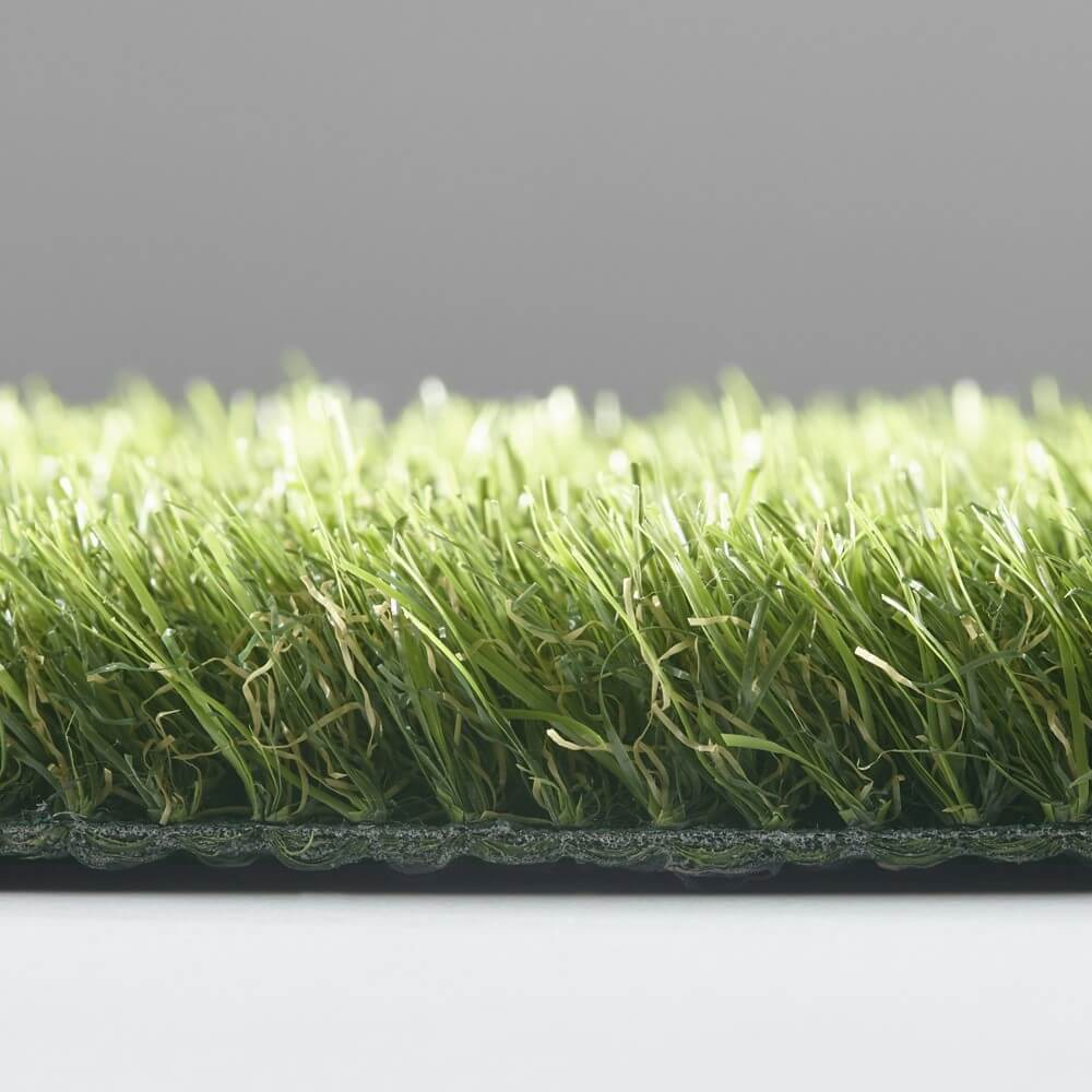 A close up of the caster artificial grass turf in front of a grey wall