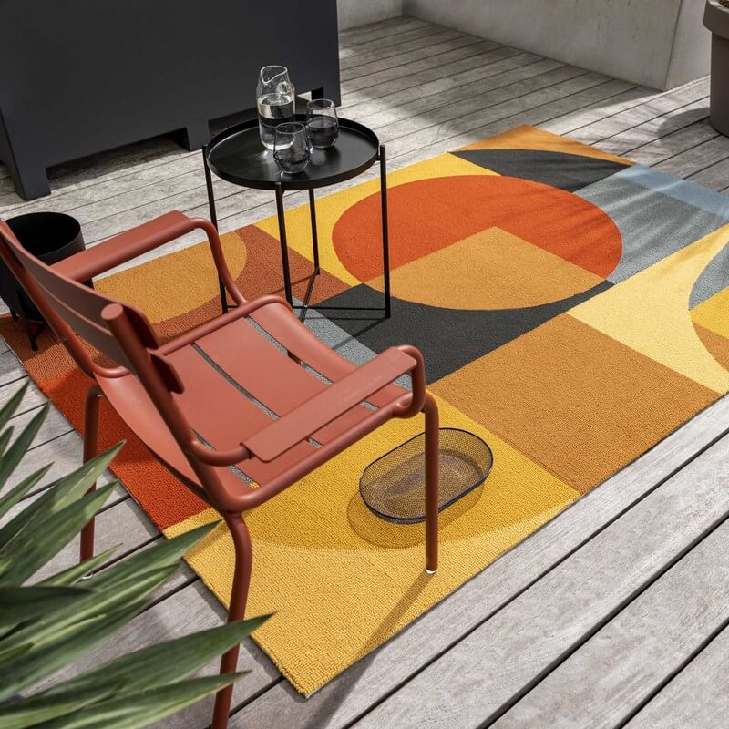 the matisse outdoor rectangular rug in geometric shapes of orange and blue sits on a wooden decking underneath a garden chair and table