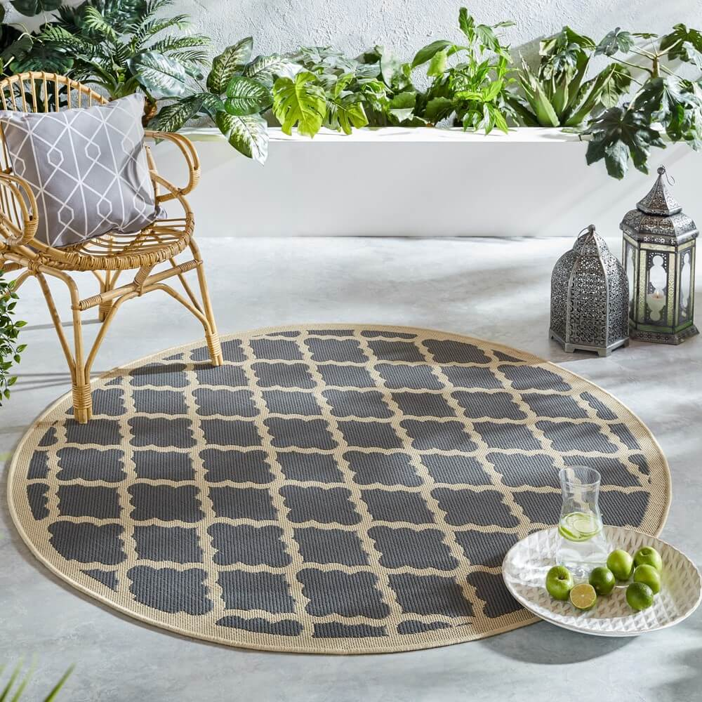 the padua circle outdoor staycation rug in beige anthracite sits on a grey wooden decking with a chair, plate of food and lantern