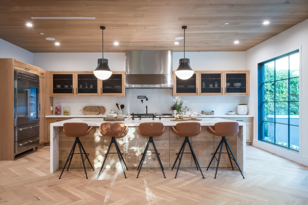 a wooden mid century modern kitchen with hanging lights and designer bar stools