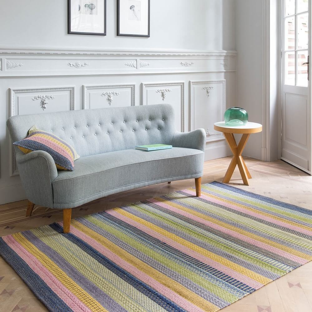 a multi coloured rug on the floor of a room with a sofa and small table