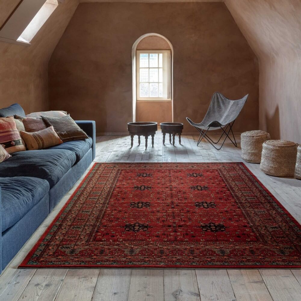 an open room with a red traditionaldining room style tug surrounded by clay coloured walls and seating