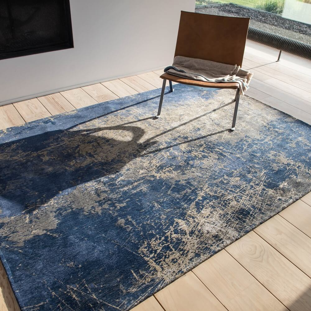 a blue cracked style rug on wooden flooring with a chair say on top