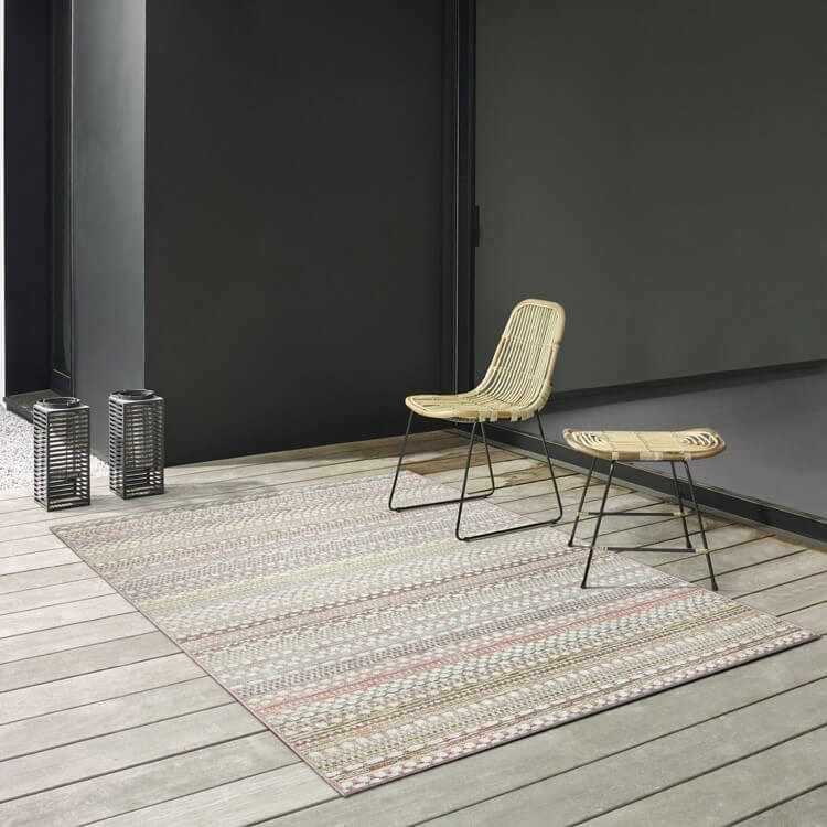 brighton modern flatweave rug on a decking with a chair, stool and lanterns