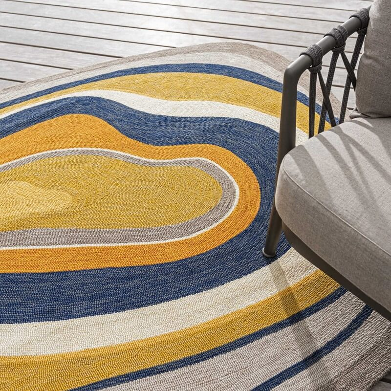 an abstract shaped rug with mustard and blue concentric circles sat on grey wooden decking with a chair on top
