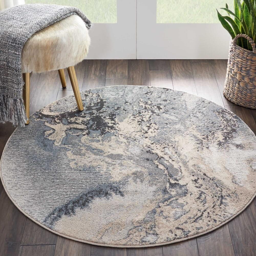 a rounded dining room rug with abstract grey swirls on a wooden floor with a matching stool and blanket