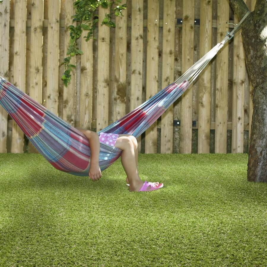 an image of the rosemary green artificial grass in a garden where someone relaxes in a hammock hanging from a tree
