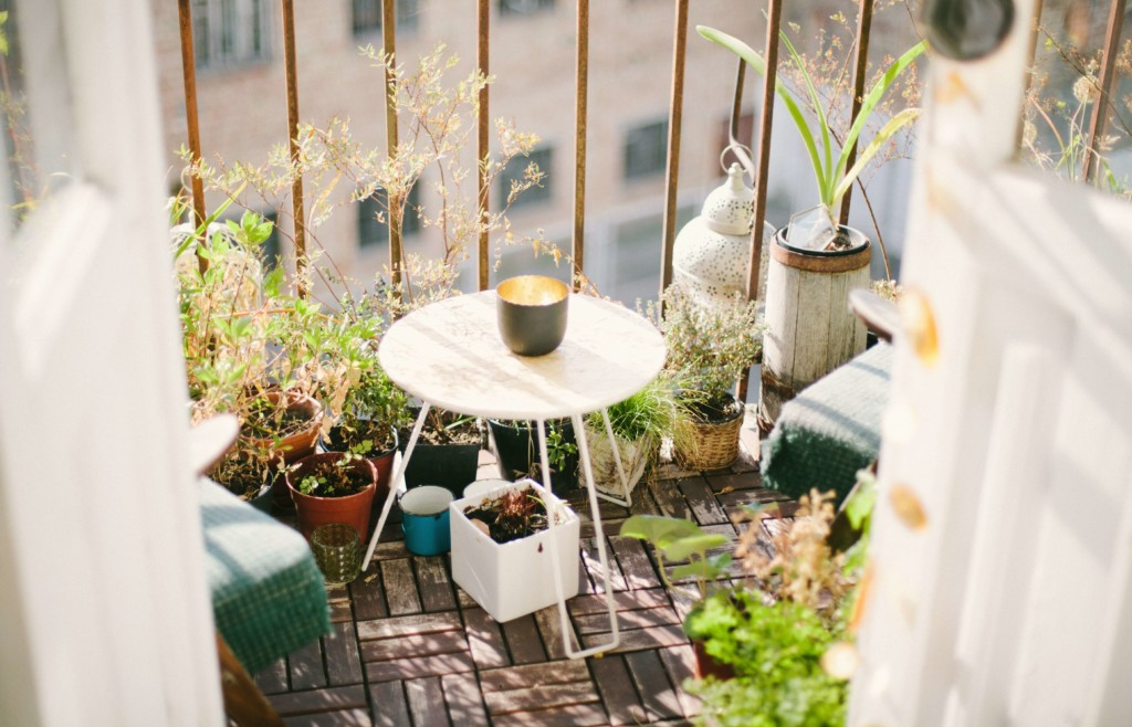 a close up of a balcony with a table and chair, surrounded by potted plants and greenery