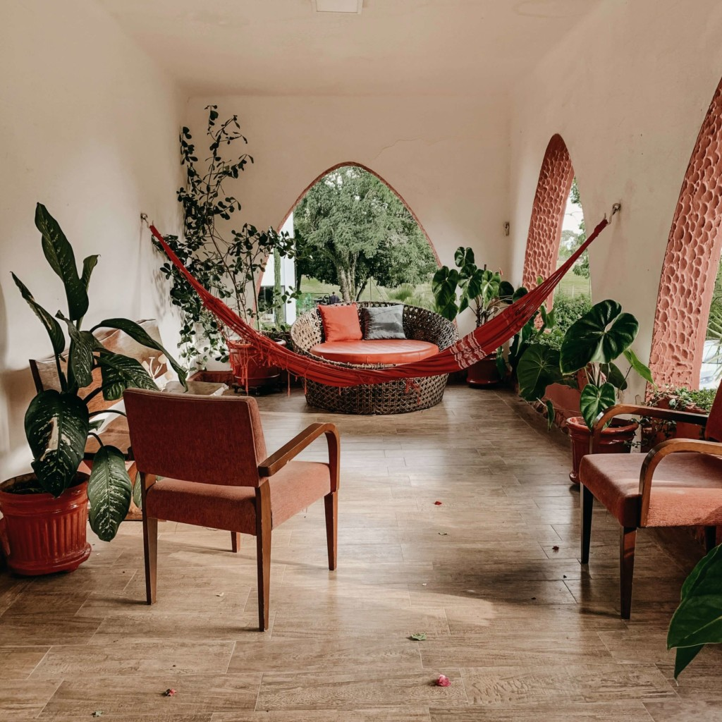 a covered balcony with a hammock, seating and cactus on a concrete floor