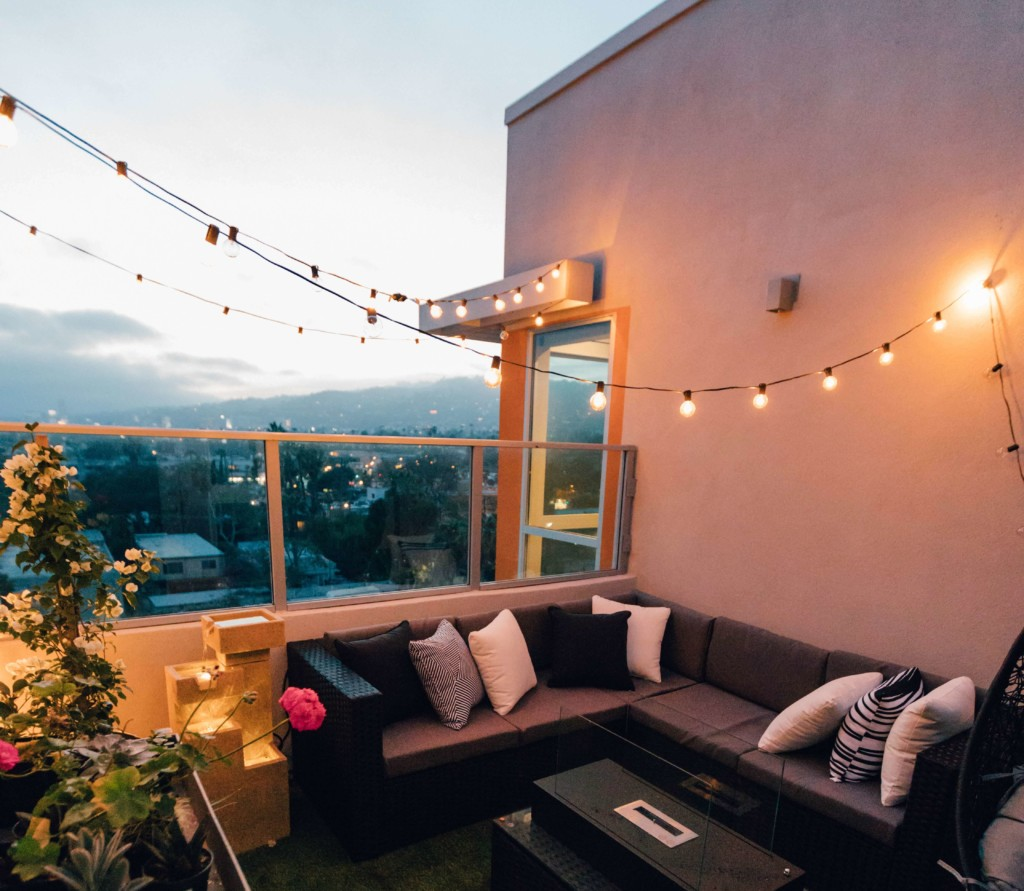 a balcony in the evening lit by bulb string lights