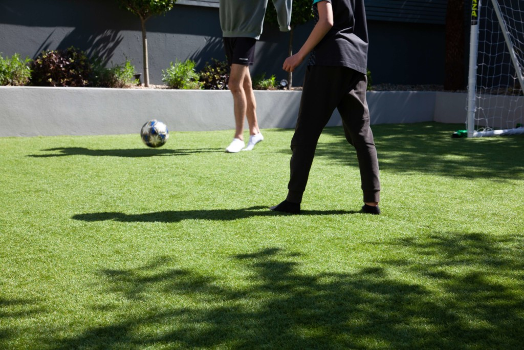 an image of two people playing football on a grassed garden