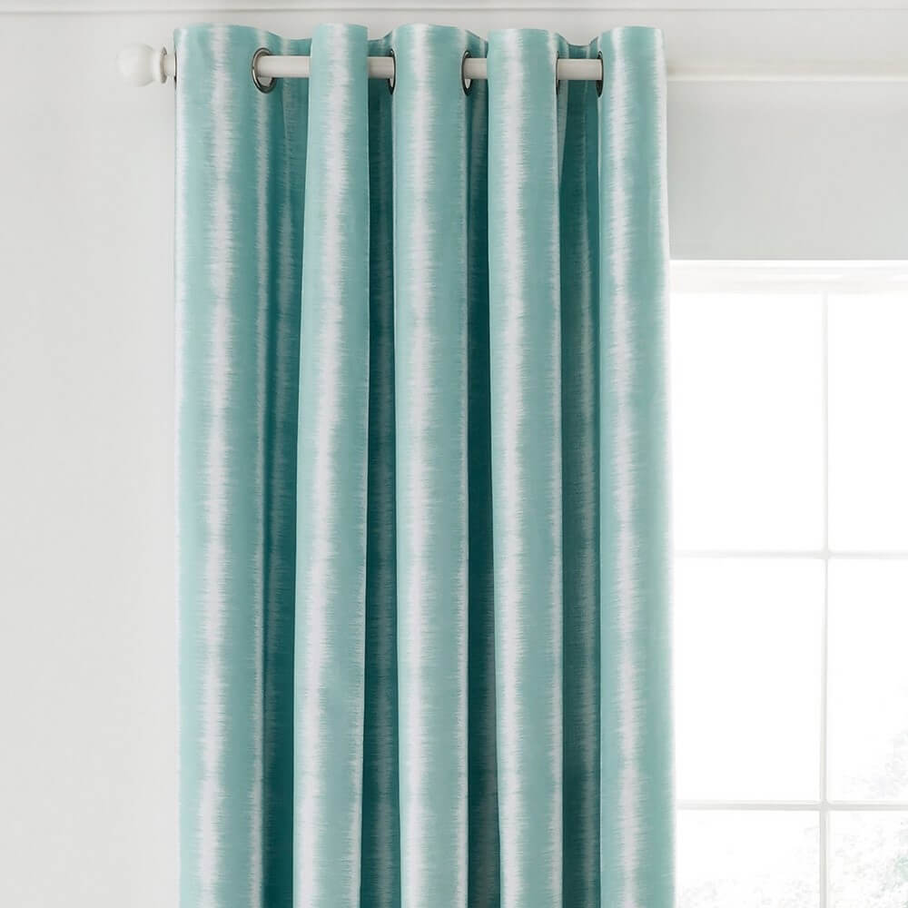 Akira scion blue textured curtains close up hanging in a window framed with a white wall