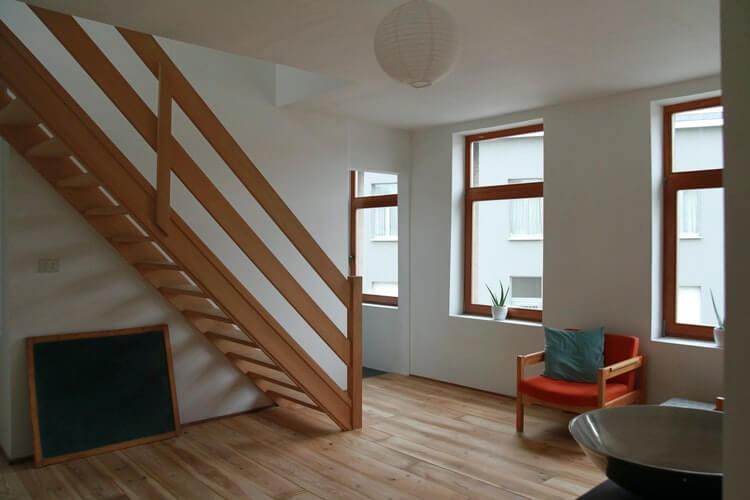 a wooden japandi style front room with stairs and large windows letting in natural light
