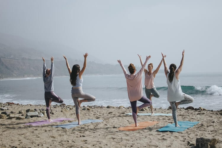 a group of people on the beach performing the yoga tree pose