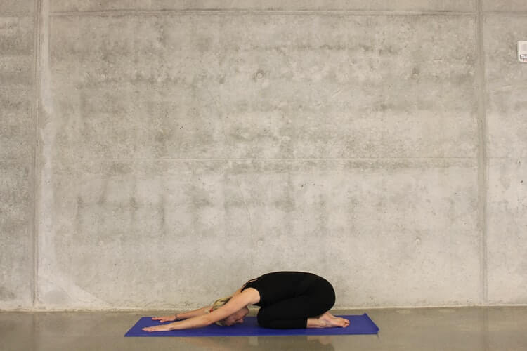 a woman on a mat performing the child's pose