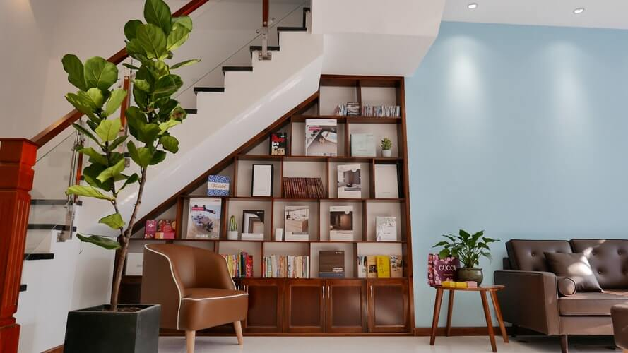 a room with a large wooden shelf to bring colour to the living room space with sofas and tables