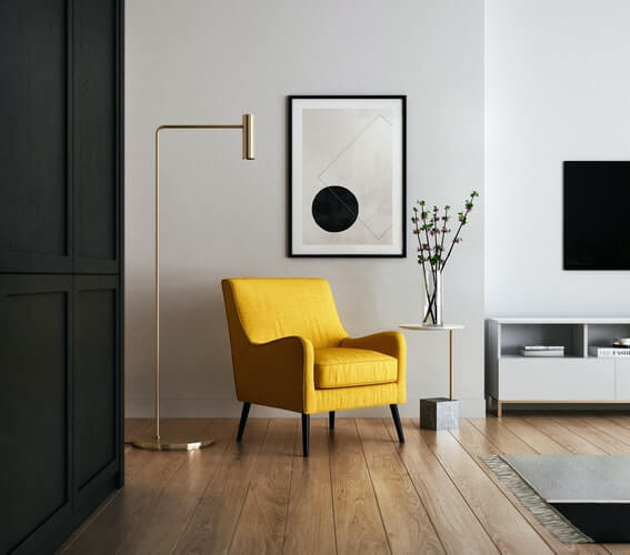 a yellow chair bringing colour to a living room space of grey and white