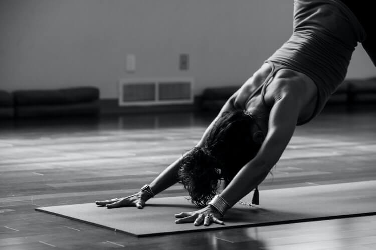 a black and white image of a woman doing the downward dog