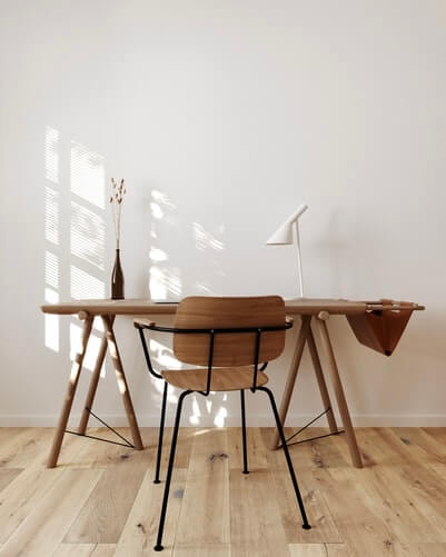 a wooden table and chairs against a white wall and wooden floor in a room flooded with natural sunshine