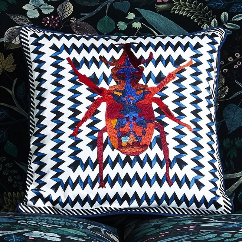 Christian Lacroix beetle wave cushion with brightly coloured embroidered stag beetle on top of a blue and white zig zag wave pattern going around the piece
