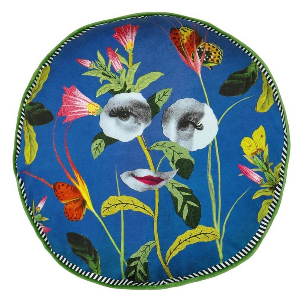 Christian Lacroix designer print rendez vous cushion with royal blue background and floral prints with black and white cut out eyes and mouth of a vintage style picture of a woman