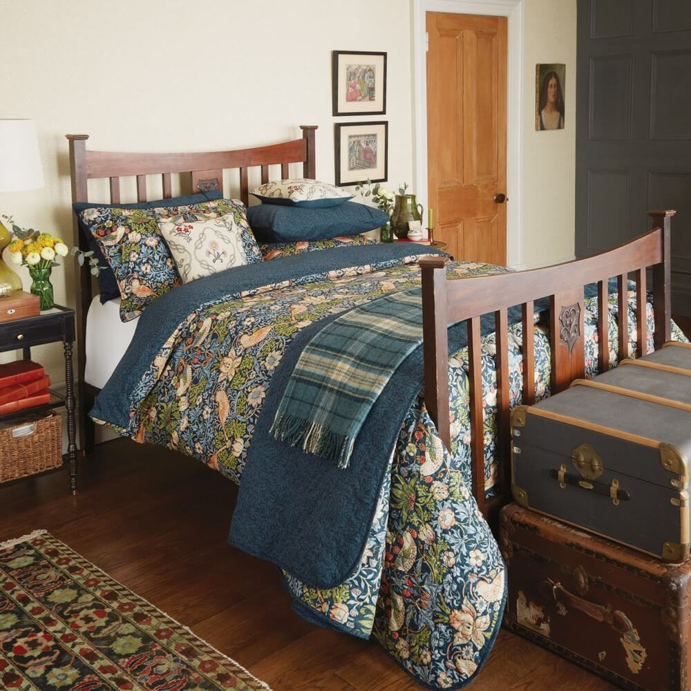 william morris strawberry print designer print bedding in an old style bedroom on a wooden bedframe