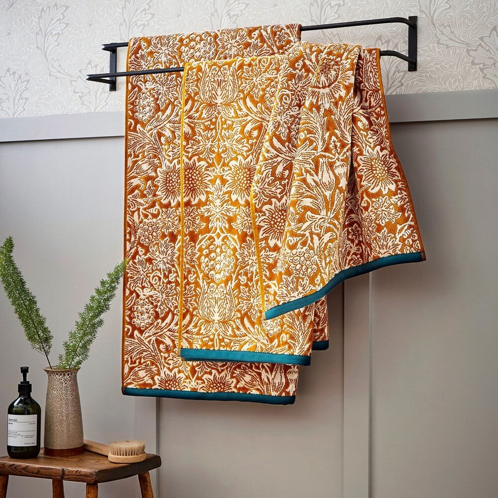 morris & co sunflower designer print towels in saffron yellow with blue hems in a grey bathroom