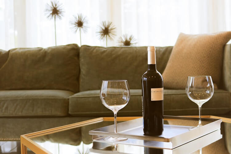 red wine bottle and glass are perched on a coffee table in a living room