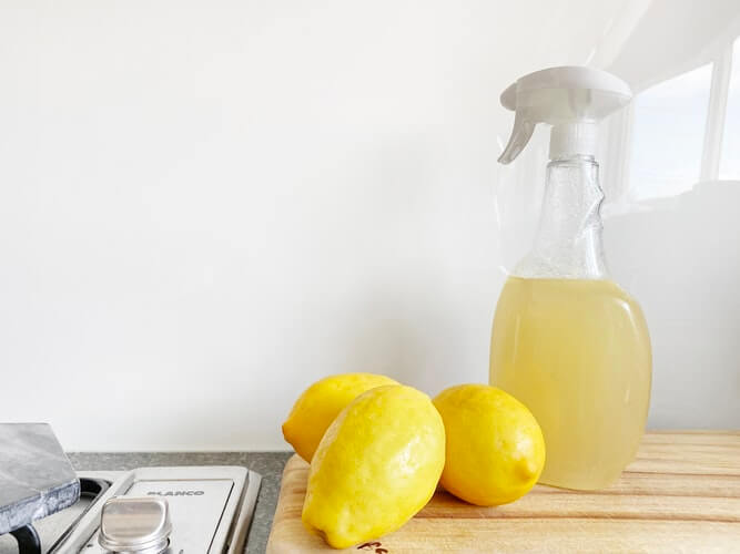 a bottle of vinegar and lemons on a table showing how to remove red wine stains