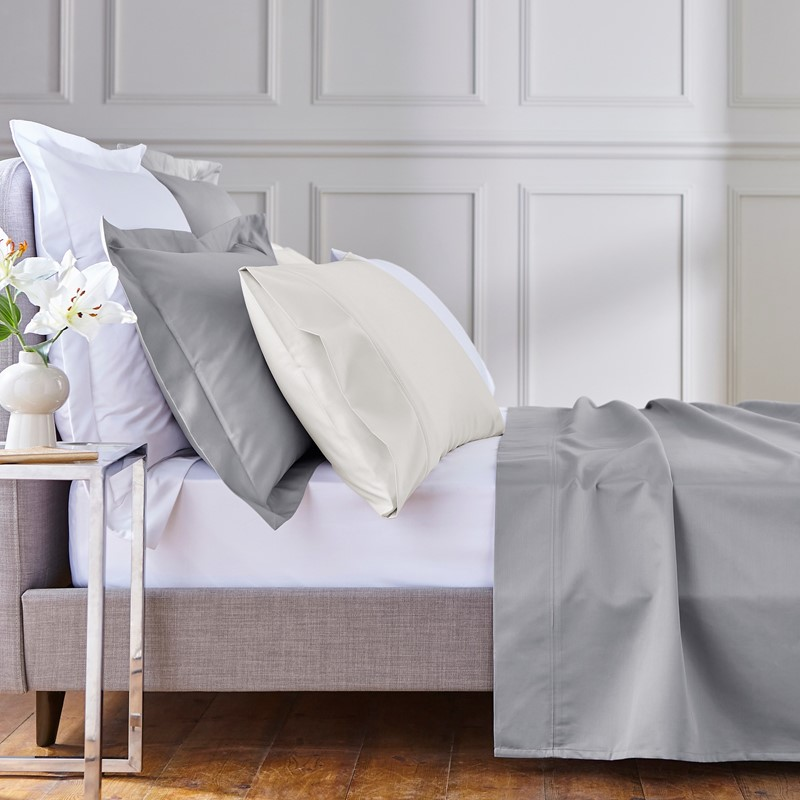 white sheet on a bed with grey bedsheets in a bedroom with home accessories
