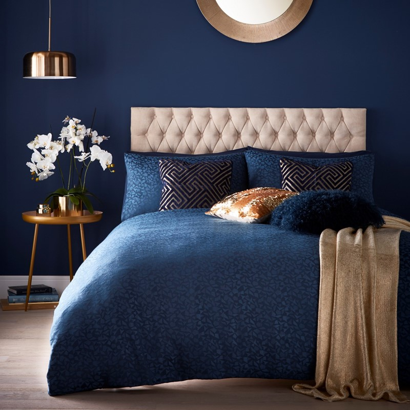 gold knit throw on the end of a dark blue bed set in a dark blue room