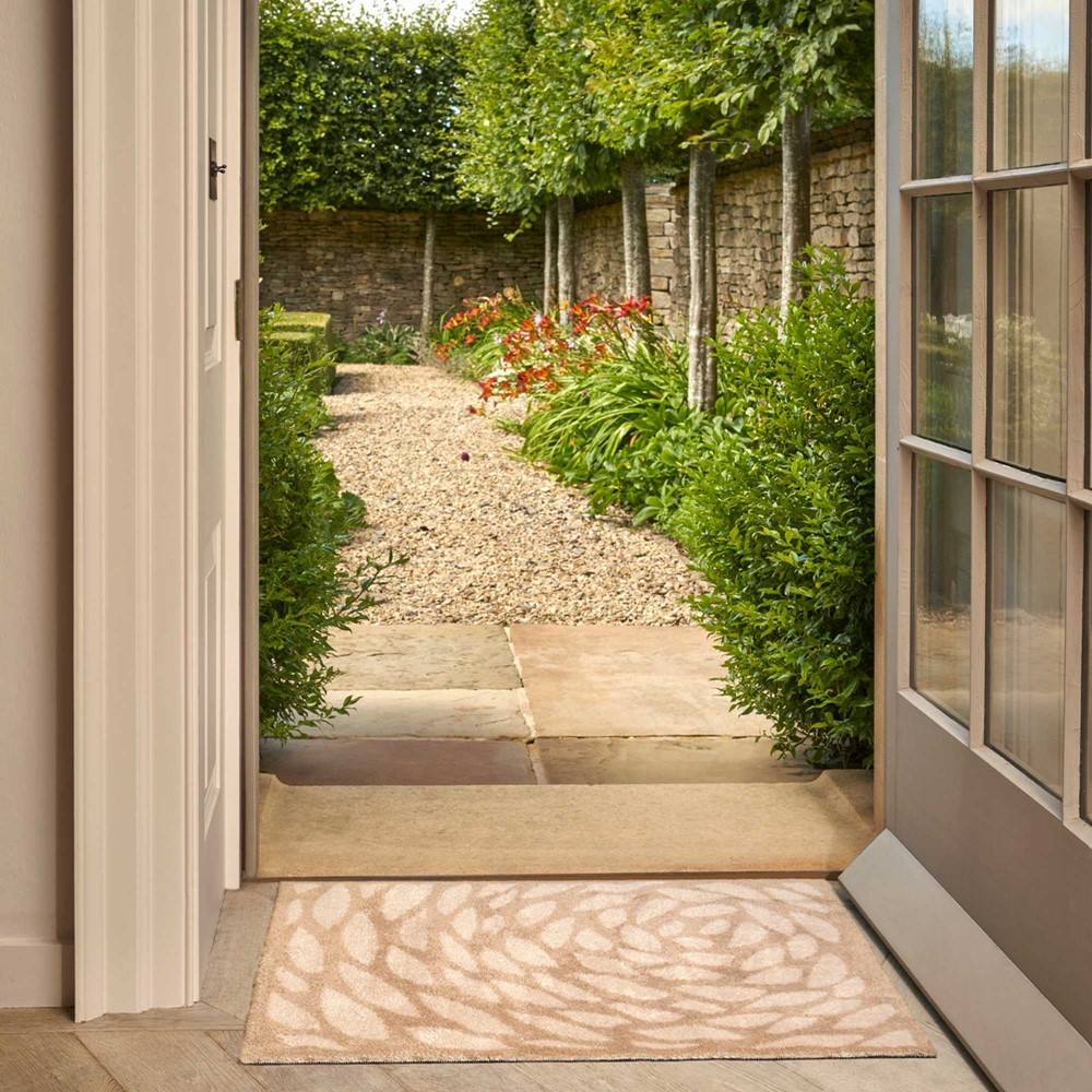 a neutral leaf shade doormat in the entry of a door