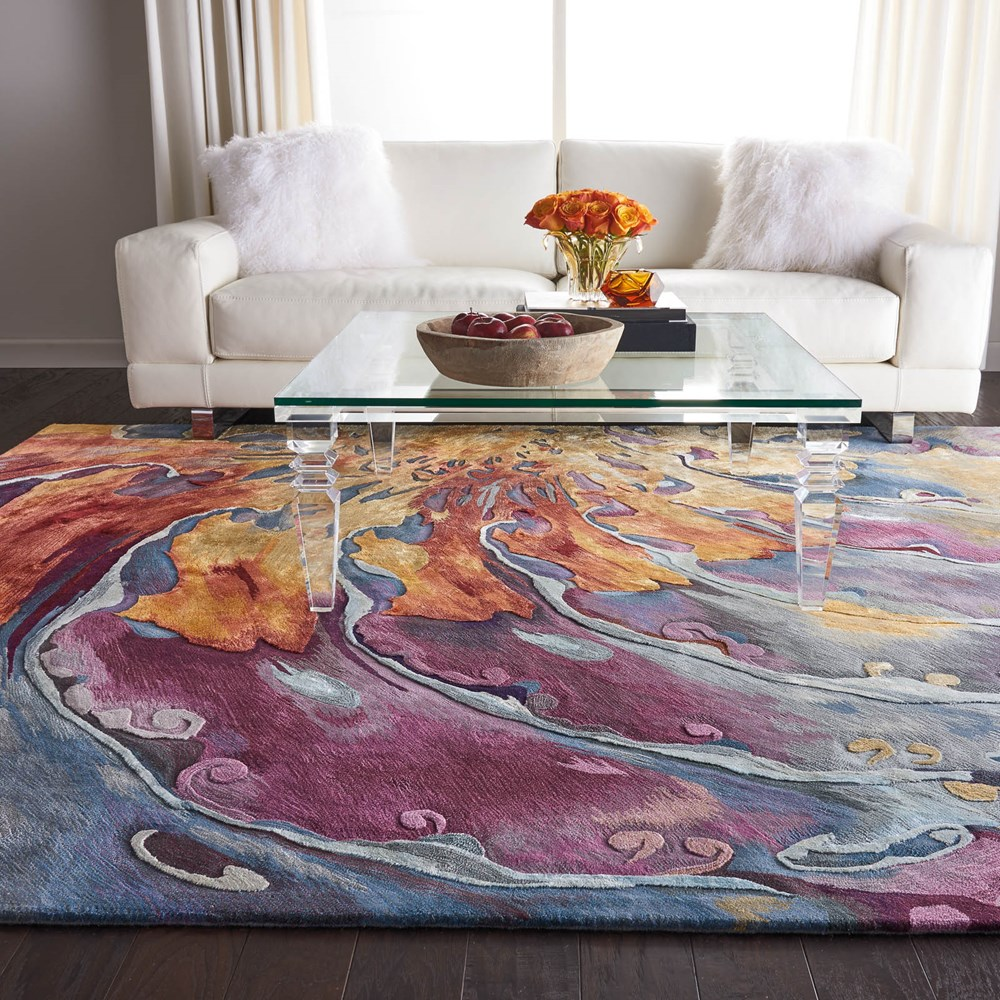 nourison multi coloured swirl style marbled rug on a wooden floor in front of a white sofa with a glass coffee table