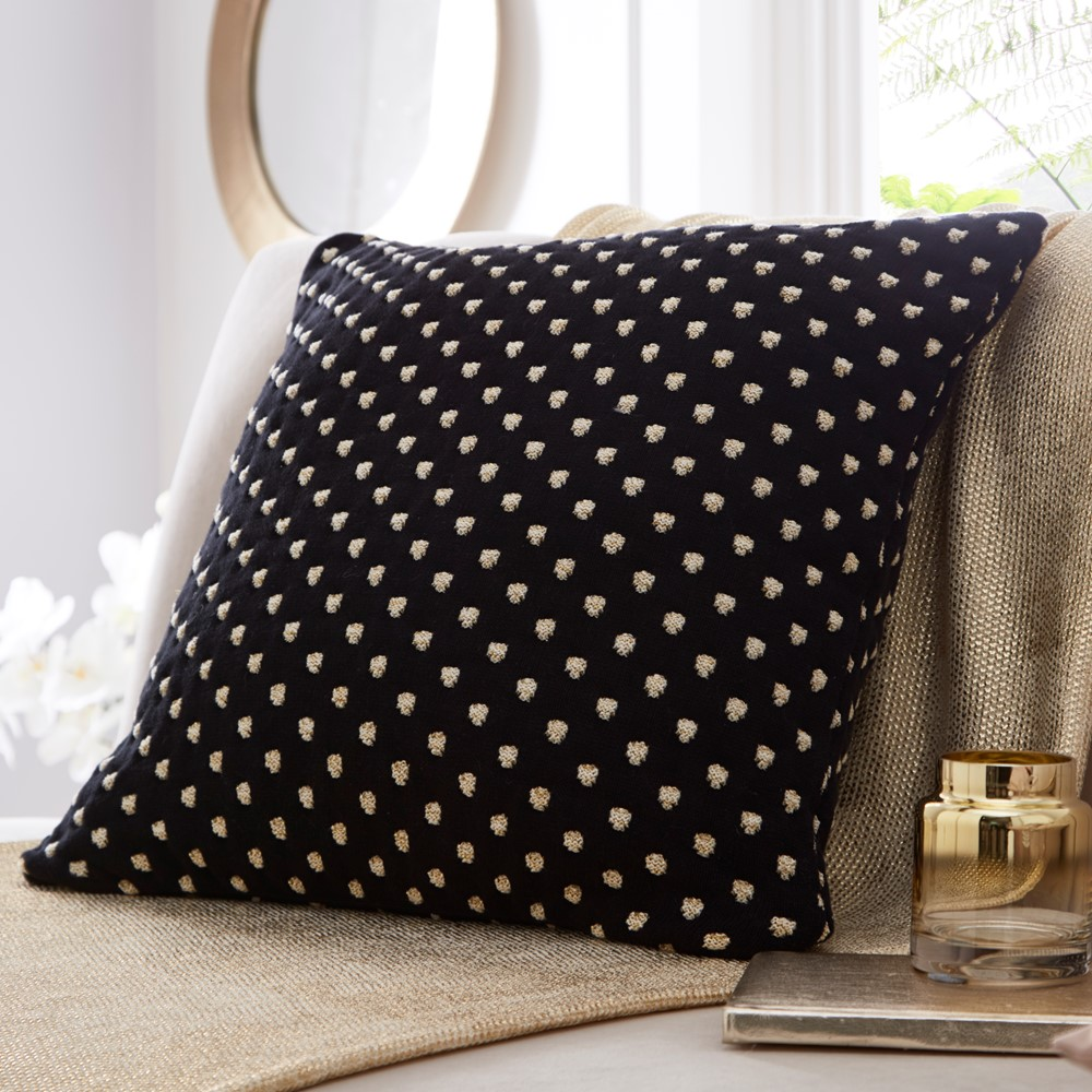 black polka dot cushion with knitted polka dots lying on a bed