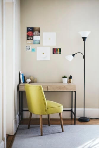 an armchair with a wooden home office desk with posters on the wall and standing light